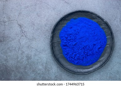 Blue spirulina powder on black stone plate. Phycocyanin extract. Natural superfood, vegan, healthy dietary supplement.