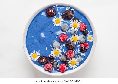 blue spirulina smoothie bowl with fresh and frozen berries, coconut and camomile flowers. healthy breakfast dessert. top view