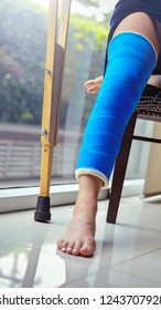 Blue splint knee. Bandaged leg cast and toes after a running injury accident.Young woman in blue plaster cast. Cropped shot of a girl holding her leg in pain. Shin splints.