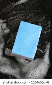 blue sponge with foam on black background