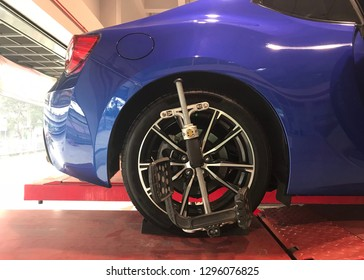 Blue sport car having modification an alignment on a platform with censor on rear wheels. Original rims.