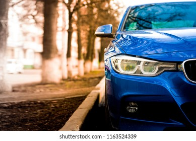 blue sports car with red tint and blurred trees in the background. Front grilles and headlights