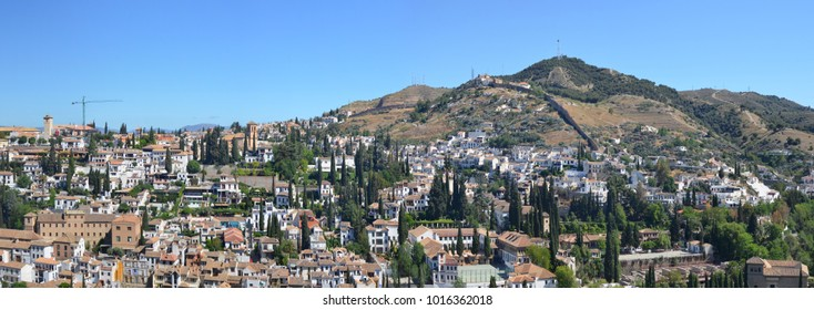 A blue spring sky over Spanish Granada town roofs.  Panoramic birds eye view landscape collage from several outdoor photos