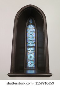 Blue stained glass narrow chapel window with black Gothic frame on a white wall