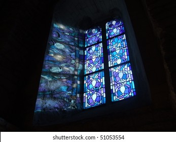 Blue stained glass window producing a colorful reflection on church wall