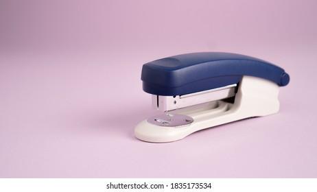 Blue stapler isolated on a purple background. Office supplies. Stapler, staple, paper, cardboard, office equipment