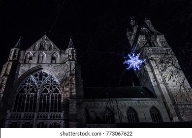 A blue star descending over a gothic church at night time. A concept of the celebration of the birth of Jezus Christ in Catholic religion. Can also be seen as a creepy, scary location to be at.