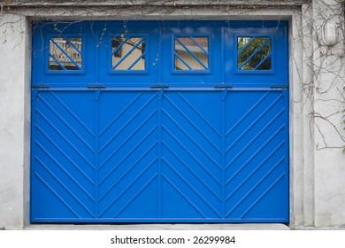 A blue steel garage door with windows