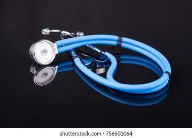 Blue stethoscope on black reflective background