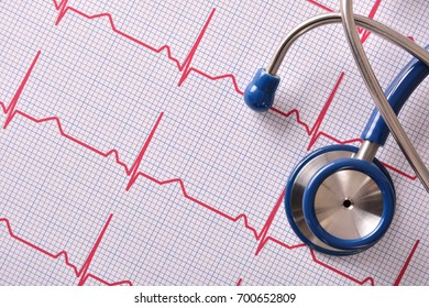 Blue stethoscope on red electrocardiogram report. Top view. Horizontal composition.