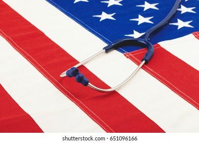 Blue stethoscope over US flag - studio shoot. Filtered image: cross processed vintage effect.
