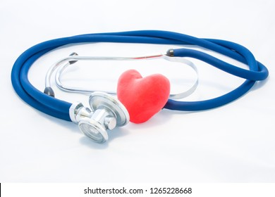 Blue stethoscope and red heart lie on white homogeneous background. Concept photo of health or pathological condition of human heart, cardiac diagnosis of diseases of heart muscle, cardiac conduction