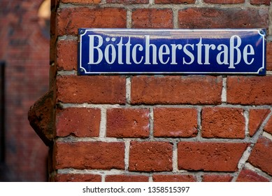 "blue street sign with white letters on a red brick wall in the old city of Bremen (Germany) - ""Böttcherstraße"" is the name of the street"