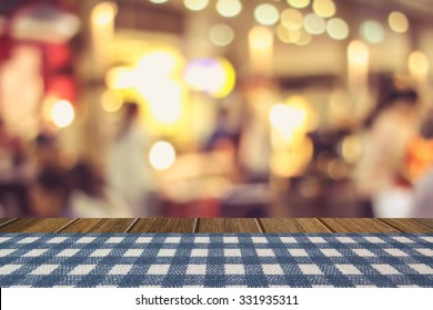 blue stripe table cloth cover on wooden table and blurry beer garden background