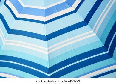 Blue striped beach umbrella closeup background