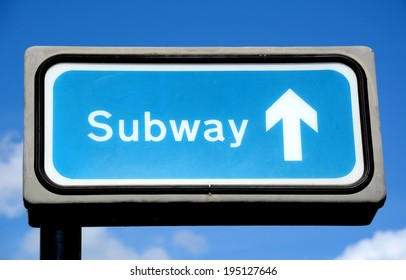 Blue subway crossing sign against the sky in London