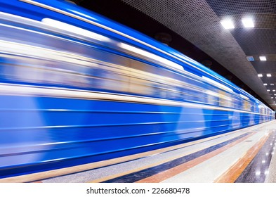Blue subway train in motion at the station