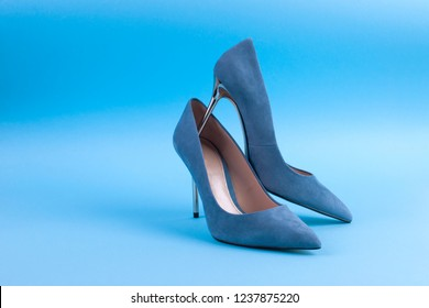 Blue suede stilettos. On a blue background. Women's elegant shoes. Free space for text. Hard light on the photo