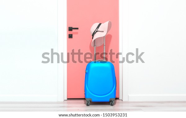 Blue suitcase with hat, near the door in the hallway. Travel concept