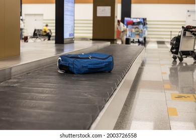 A blue suitcase on a conveyor belt at the international airport. Baggage claim point. Baggage claim at the airport