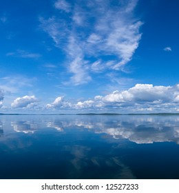Blue summer bright sky reflecting in lake