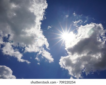 Blue summer sky with sunbeams and clouds