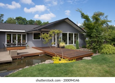 A blue summer sky with white clouds makes the perfect background for this portrait of a contemporary home featuring a deck that spans a water feature emulating a rock lined stream.