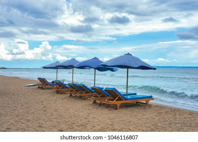 Blue sun loungers with open umbrellas in a row on a beach in Canggu. Bali, Indonesia