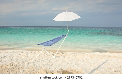 Blue sunbed with small parasol positioned on the sandy beach next to azure blue water