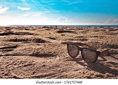 Blue sunglasses lay on the beach