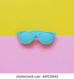 blue sunglasses on pink and yellow background. minimalism and summer fashion for the beach