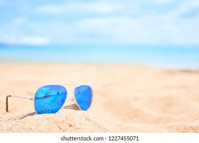Blue sunglasses on sand beach. Vacation concept