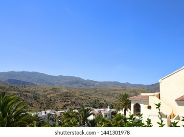 Blue sunny sky, distant mountain villas surrounded by green exotic plants, palm trees