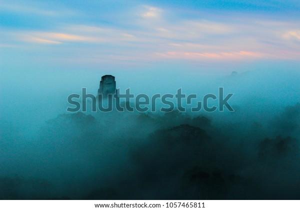 Blue sunrise at mayan temple in Tikal, Guatemala, rain forest, foggy
