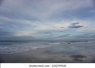 Blue sunset scene on the beach with sand & tidal waves