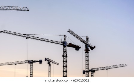 blue sunset sky after five big high cranes under a new construction site of high-rise building against blue sunset sky. three lonely metal cranes bottom view