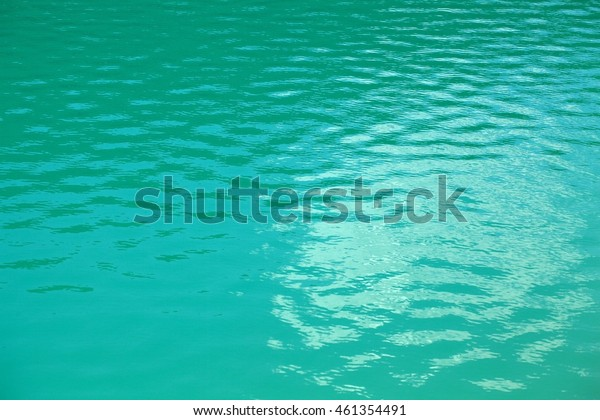 The blue surface of an alpine lake with light waves.