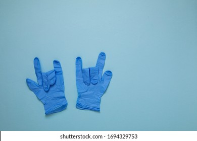 Blue surgical gloves showing rock sign gesture, fight Coronavirus concept