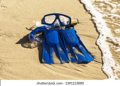 Blue Swim flippers, mask, snorkel for  surf laing on the sandy beach. beach  concept, for summer or holidays background