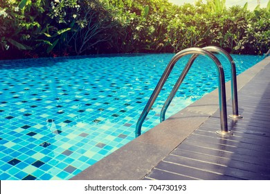 blue swimming pool around with green nature garden, place of outdoor activity relaxation in summer day, image used sunlight vintage filter effect