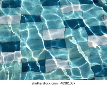 blue swimming pool tiles under water with sunlight patterns