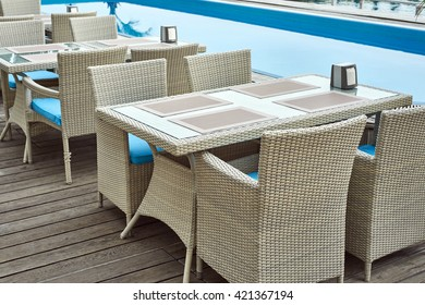 Blue swimming pool with wood flooring next to cafe