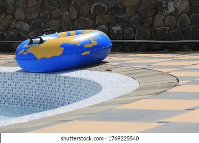 a blue swimming tire floater beside the pool