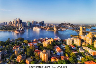 Blue Sydney Harbour surrounded by shores of Sydney city CBD and Lower NOrth Shore suburb Kirribilli connected by the Sydney Harbour bridge in elevated aerial view.