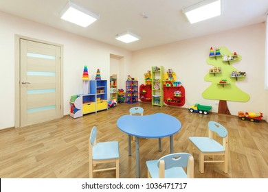 Blue table for classes with children and light pink colored game room with in the kindergarten.