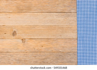 Blue table cloth, rustic checkered fabric on wood background, top view, copy space.
