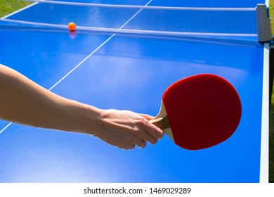 Blue table tennis or ping pong. Playing ping pong. Close up ping pong net and line. Table tennis or ping pong rackets or paddle  and ball on a blue table with hand.
