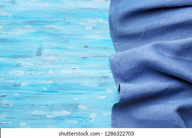Blue tablecloth from right side of turquoise wooden table top view with copy space