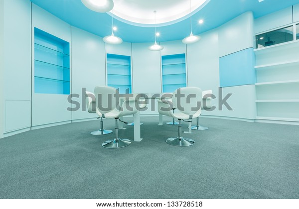 blue tables and white chairs under white ceiling lamps in the empty modern library