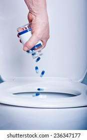 Blue tablets being thrown away to the toilet.